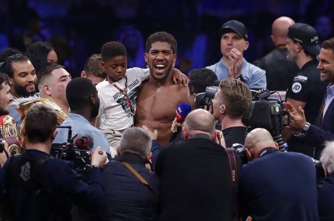 Britain's Anthony Joshua celebrates after beating Andy Ruiz Jr. to win their World Heavyweight Championship contest at the Diriyah Arena, Riyadh, Saudi Arabia early Sunday Dec. 8, 2019. (AP Photo/Hassan Ammar)