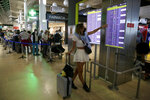 A woman points at a screen showing departing flights, many of them canceled, at Lisbon airport, Saturday, July 17, 2021. A strike by ground handling workers at Portugal's airports forced the cancellation of over 200 flights on Saturday. The walkouts over wage conditions are scheduled to last through Sunday. (AP Photo/Armando Franca)