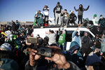 Philadelphia Eagles stand atop a news van while waiting for the team to deplane Monday, Feb. 5, 2018, at Philadelphia International Airport a day after defeating the New England Patriots in Super Bowl 52. (AP Photo/Julio Cortez)