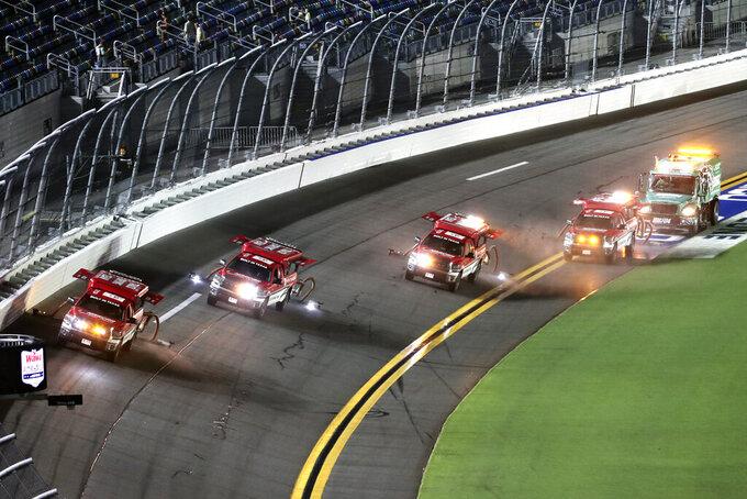 Track dryers make their way around the speedway during a rain delay at a NASCAR Xfinity Series auto race at Daytona International Speedway, Friday, Aug. 27, 2021, in Daytona Beach, Fla. (AP Photo/David Graham)