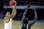 Maryland guard Eric Ayala, left, shoots against Nebraska forward Lat Mayen during the second half of an NCAA college basketball game, Tuesday, Feb. 16, 2021, in College Park, Md. Maryland won 64-50. (AP Photo/Julio Cortez)