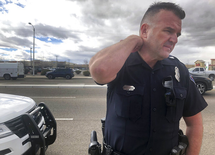 Officer Simon Drobik answers questions about an explosion that he says killed one person in Albuquerque, N.M., on Monday, Feb. 4, 2019. Police say they are investigating the explosion that happened in an alley behind a strip mall with a grocery store, pharmacy and several other businesses. (AP Photo/Mary Hudetz)
