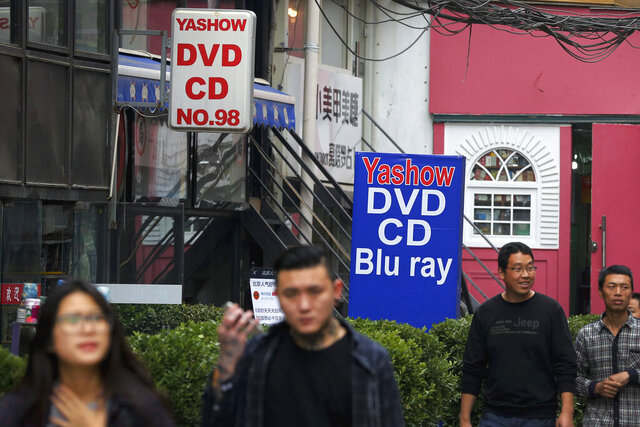 FILE - In this April 27, 2016, file photo, people walk past a shop selling pirated movie DVDs and music CDs in Beijing. China's leaders have issued new, tougher guidelines for protection of patents, copyrights and other intellectual property. (AP Photo/Andy Wong, File)