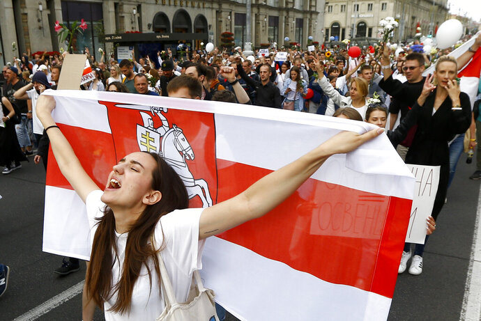 A woman reacts as she marches holding an old Belarusian national flag in the center of Minsk, Belarus, Friday, Aug. 14, 2020.  Some thousands of people have flooded the cnetre of the Belarus capital, Minsk, in a show of anger over a brutal police crackdown this week on peaceful protesters that followed a disputed election. (AP Photo/Sergei Grits)