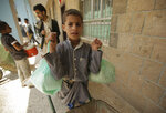 A boy carries food supplies provided by the World Food Programme at a school in Sanaa, Yemen, Sunday, Aug. 25, 2019. The U.N. humanitarian chief in Yemen warned last Wednesday that unless significant new funding is received in the coming weeks, food rations for 12 million people in the war-torn country will be reduced and at least 2.5 million malnourished children will be cut off from life-saving services. (AP Photo/Hani Mohammed)