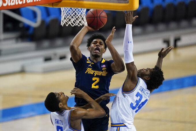 Marquette forward Justin Lewis, center, goes up for a shot against UCLA guard Chris Smith, left, and UCLA guard David Singleton (34) during the first half of an NCAA college basketball game Friday, Dec. 11, 2020, in Los Angeles. (AP Photo/Ashley Landis)