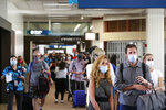Visitors line a corridor in the Daniel K. Inouye International Airport as they enter the state, Thursday, Oct. 15, 2020, in Honolulu. A new pre-travel testing program will allow visitors who test negative for COVID-19 to come to Hawaii and avoid two weeks of mandatory quarantine goes into effect Thursday. The pandemic has caused a devastating downturn on Hawaii's tourism-based economy. Coronavirus weary residents and struggling business owners in Hawaii will be watching closely as tourists begin to return to the islands. (AP Photo/Marco Garcia)