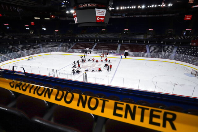 Calgary Flames' players take to the ice during NHL hockey practice in Calgary, Alberta, Monday, July 13, 2020. (Jeff McIntosh/The Canadian Press via AP)