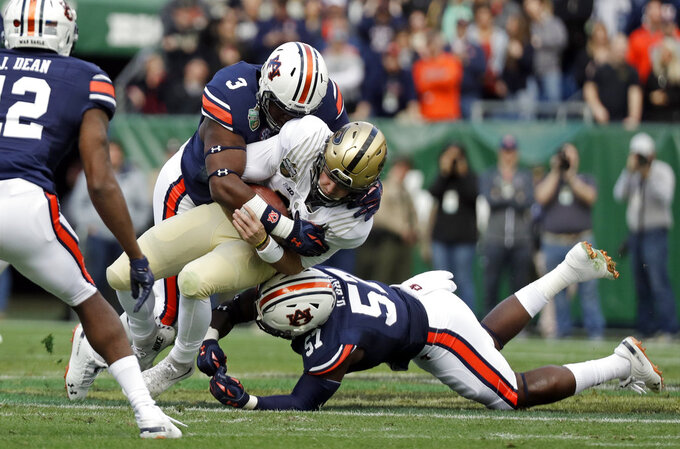 Purdue quarterback David Blough is hit by Auburn defenders Marlon Davidson (3) and Deshaun Davis (57) in the first half of the Music City Bowl NCAA college football game Friday, Dec. 28, 2018, in Nashville, Tenn. (AP Photo/Mark Humphrey)