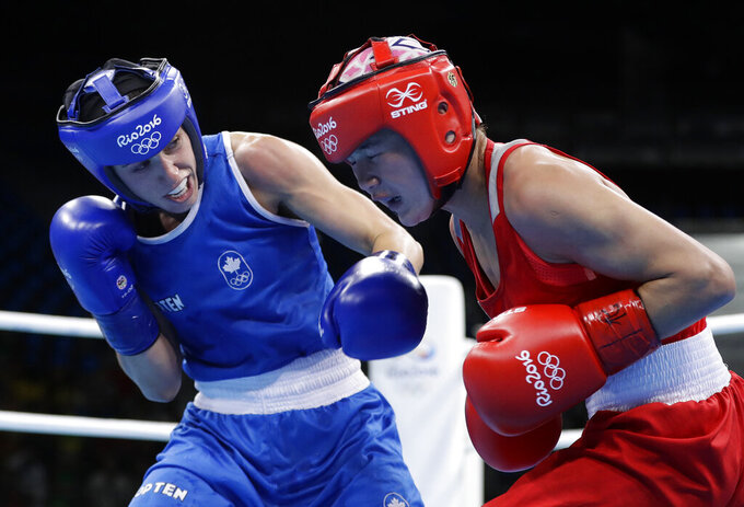 FILE - In this Aug. 2, 2016, file photo, Canada's Mandy Bujold, left, knocks down Uzbekistan's Yodgoroy Mirzaeva during a women's flyweight 51-kg preliminary boxing match at the Summer Olympics in Rio de Janeiro, Brazil. The Tokyo Olympics fate for Canada's best boxer lies in the hands of the Court of Arbitration for Sport after her qualifying tournament was scrapped due to the pandemic. Bujold and her lawyer, Sylvie Rodrigue, lost their appeal to the International Olympic Committee earlier this week, leaving CAS as her last chance to box in what would be her final Olympics. (AP Photo/Frank Franklin II, File)