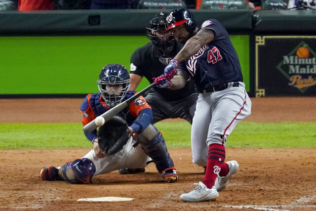 FILE - In this Oct. 30, 2019, file photo, Washington Nationals' Howie Kendrick hits a two-run home run against the Houston Astros during the seventh inning of Game 7 of the baseball World Series in Houston. The Astros were scheduled to spend July 4 in the nation's capital during a three-game series against the defending World Series champion Nationals. Houston won all three games at Nationals Park last October. But the Nationals won every game at Minute Maid Park, with Kendrick's two-run home run in the seventh inning of Game 7 putting them ahead to stay. (AP Photo/Eric Gay, File)