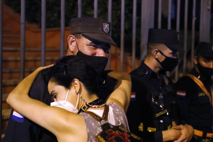 A woman embraces a police officer as people protest, calling for the resignation of President Mario Abdo Benitez over his handling of the coronavirus pandemic and the state of the public health system, in Asuncion, Paraguay, Monday, March 8, 2021. (AP Photo/Jorge Saenz)