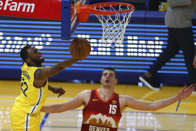 Golden State Warriors' Andrew Wiggins, left, shoots against Denver Nuggets' Nikola Jokic at an NBA basketball game in San Francisco, Friday, April 23, 2021. (AP Photo/Jed Jacobsohn)