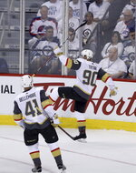 Las Vegas Golden Knights' Tomas Tatar (90) celebrates with Pierre-Edouard Bellemare (41) after Tatar scored on Winnipeg Jets goaltender Connor Hellebuyck (37) during first period game 2 NHL Western Conference Finals hockey action in Winnipeg, Manitoba, Monday, May 14, 2018. (Trevor Hagan/The Canadian Press via AP)