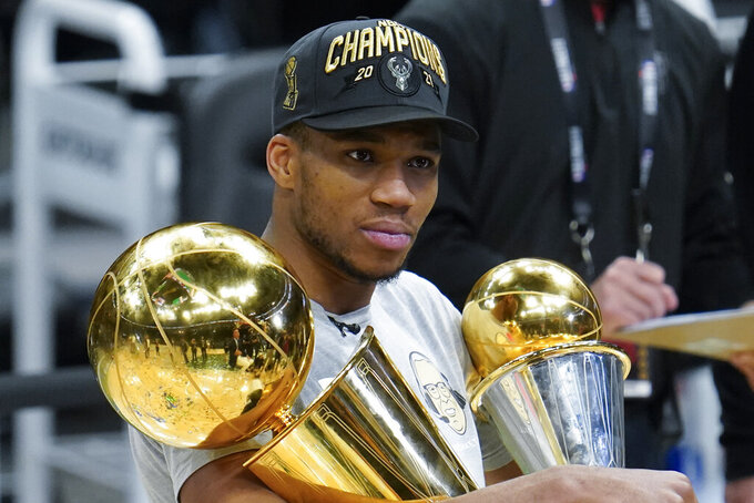 FILE - In this July 20, 2021, file photo, Milwaukee Bucks forward Giannis Antetokounmpo holds the NBA Championship trophy, left, and Most Valuable Player trophy after defeating the Phoenix Suns in Game 6 of basketball's NBA Finals in Milwaukee. One month after leading the Bucks to their first NBA title in half a century, Antetokounmpo is teaming up with the city's other major pro sports franchise by joining the Milwaukee Brewers' ownership group. (AP Photo/Paul Sancya, File)