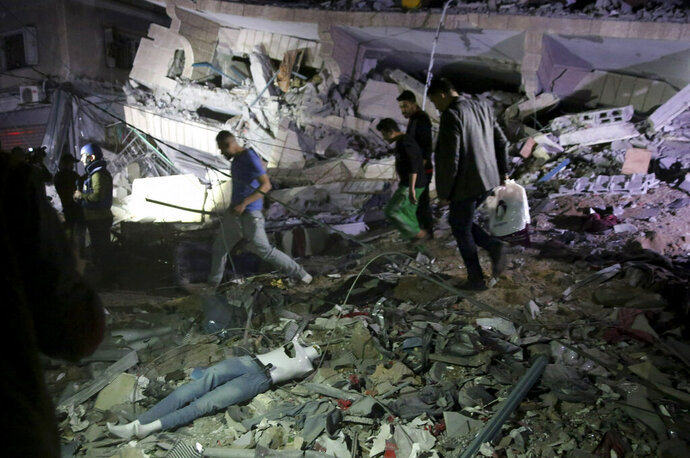 Owners of stores at the building inspect the damage of their destroyed multi-story building in Gaza City, Saturday, May 4, 2019. Palestinian militants on Saturday fired over 200 rockets into Israel, drawing dozens of retaliatory airstrikes on targets across the Gaza Strip in a round of intense fighting that broke a monthlong lull between the bitter enemies. Three Palestinians, including a mother and her baby daughter, were killed, while three Israelis, including an 80-year-old woman, were wounded by rocket fire. (AP Photo/Adel Hana)