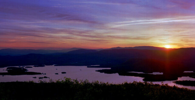 FILE - In this May 19, 1998, file photo, the sun sets on Squam Lake, as seen from Red Hill in Moultonborough, N.H. New Hampshire filed a lawsuit Tuesday, Oct. 27, 2020, against the agrochemical giant Monsanto over what it says has been widespread PCB pollution in the state. The state said PCBs have fouled about numerous square miles of the Atlantic Ocean and 46 other water bodies including Squam Lake and stretches of the Souhegan River. (AP Photo/Jim Cole, File)