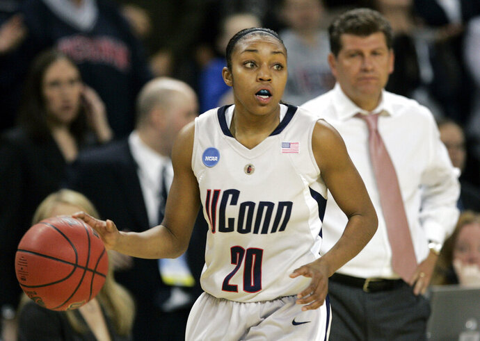 FILE - In this March 31, 2009, file photo, Connecticut guard Renee Montgomery brings the ball up during the second half of a women's NCAA college basketball tournament regional final against Arizona State in Trenton, N.J. At rear is Connecticut coach Gene Auriemma. Montgomery and Tiffany Hayes appreciated what former UConn teammate Maya Moore was doing when the All-Star forward stepped away from basketball two years ago to focus on criminal justice reform. The Atlanta Dream guards admit they weren't sure why she couldn't continue keep playing at the same time. Now they have a better understanding. (AP Photo/Mel Evans, File)