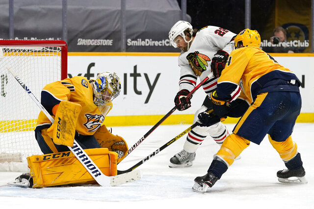 Chicago Blackhawks center Ryan Carpenter (22) scores a goal against Nashville Predators goaltender Juuse Saros (74) in the third period of an NHL hockey game Wednesday, Jan. 27, 2021, in Nashville, Tenn. (AP Photo/Mark Humphrey)
