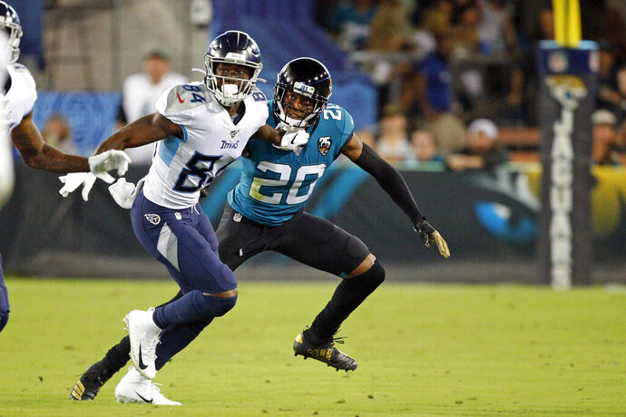 Jacksonville Jaguars cornerback Jalen Ramsey (20) covers Tennessee Titans wide receiver Corey Davis (84) as he runs a pattern during the first half of an NFL football game, Thursday, Sept. 19, 2019, in Jacksonville, Fla. (AP Photo/Stephen B. Morton)