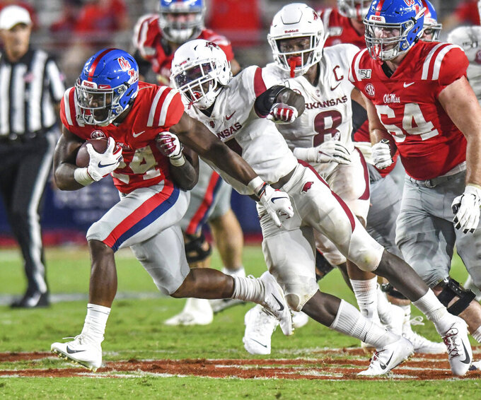 Mississippi running back Snoop Conner (24) is hit by Arkansas defensive back Joe Foucha (7) during an NCAA college football game Saturday, Sept. 7, 2019, in Oxford, Miss. (Bruce Newman/The Oxford Eagle via AP)
