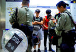 Riot police check passengers' bags at airport express central station in downtown Hong Kong, Saturday, Sept. 7, 2019. Hong Kong authorities were limiting airport transport services and controlling access to terminals Saturday as they braced for a second weekend of disruption following overnight demonstrations that turned violent. (AP Photo/Vincent Yu)
