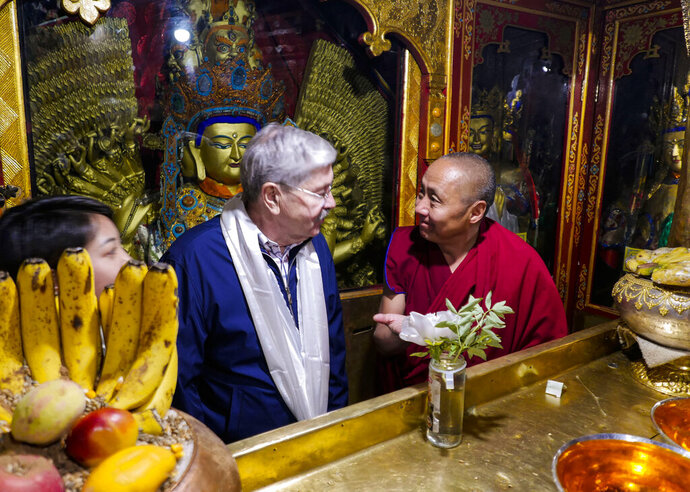 FILE - In this file photo taken May 23, 2019, and released by the U.S. Embassy in Beijing, U.S. Ambassador to China Terry Branstad, left, speaks with a monk at the Jokhang Temple in Lhasa in western China's Tibet Autonomous Region. China said Wednesday, Jul 8, 2020, it will impose visa restrictions on U.S. individuals following the Trump administration's imposition of travel bans on Chinese officials it accuses of restricting foreigners' access to Tibet. (U.S. Mission to China via AP, File)