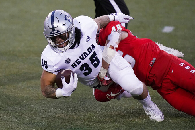 New Mexico linebacker Brandon Shook (46) tackles Nevada running back Toa Taua (35) during the first half of an NCAA college football game Saturday, Nov. 14, 2020, in Las Vegas. (AP Photo/John Locher)