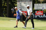 Tiger Woods, right, walks with his caddie, Joe LaCave, after play was suspended due to weather during the second round of the PGA Championship golf tournament at Bellerive Country Club, Friday, Aug. 10, 2018, in St. Louis. (AP Photo/Jeff Roberson)
