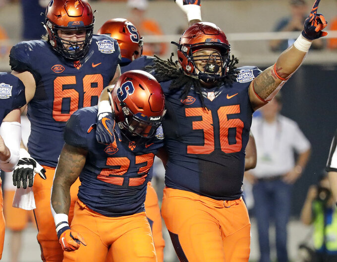 Syracuse fullback Chris Elmore (36) celebrates with running back Abdul Adams (23) after Adams scored a touchdown on a 3-yard run against West Virginia during the first half of the Camping World Bowl NCAA college football game Friday, Dec. 28, 2018, in Orlando, Fla. (AP Photo/John Raoux)