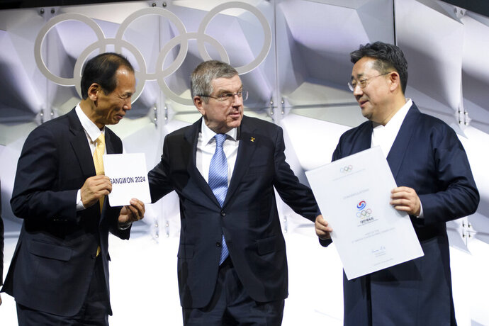 From left Choi Moon-soon governor of Gangwon Province, Thomas Bach, president of the International Olympic Committee (IOC), and Park Yang-woo, Minister of the Ministry of Culture, Sports and Tourism of Korea, show the name of Gangwon Province in South Korea during the 135th Session of the International Olympic Committee (IOC) on the sideline of the the 3rd Winter Youth Olympic Games Lausanne 2020, at the SwissTech Convention Centre, in Lausanne, Switzerland, Friday, Jan. 10, 2020 after Gangwon was elected to host the 4th Winter Youth Olympic Games 2024. (Laurent Gillieron/Keystone via AP)