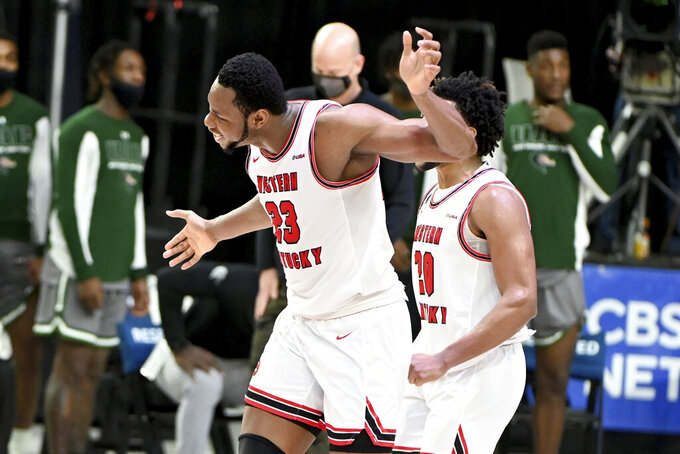 Western Kentucky center Charles Bassey (23) celebrates his teams 64-60 win in an NCAA college basketball game in the Conference USA men's tournament, in Frisco, Texas, Friday, March 12, 2021. (AP Photo/Matt Strasen)