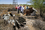 In this photo taken on Thursday, Nov. 14, 2019, small scale farmers gather at a broken windmill where they have to pump underground water in Vosburg, South Africa. The worst drought some farmers have seen in decades is affecting much of southern Africa. The United Nations says more than 11 million people now face crisis levels of food insecurity. (AP Photo/Denis Farrell)