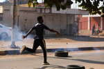 A protester runs at a demonstration, in Khartoum, Sudan, Wednesday, Oct. 21, 2020. Protesters have taken to the streets in the capital and across the country over dire living conditions and a deadly crackdown on demonstrators in the east earlier this month. Sudan is currently ruled by a joint civilian-military government, following the popular uprising that toppled longtime autocrat Omar al-Bashir last year. (AP Photo/Marwan Ali)