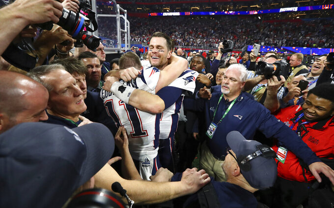 In this Sunday, Feb. 3, 2019, photo New England Patriots' Julian Edelman and Tom Brady celebrate after the NFL Super Bowl 53 football game against the Los Angeles Rams in Atlanta. The Patriots won 13-3. Edelman was named the Most Valuable Player. (Curtis Compton/Atlanta Journal-Constitution via AP)