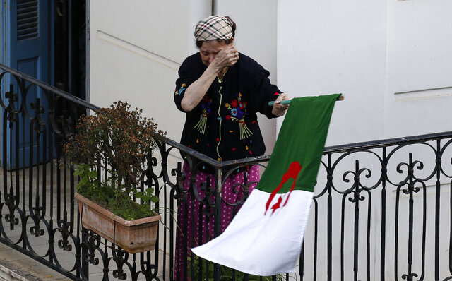 A woman wipes her face while carrying a national flag as protesters take to the streets in the capital Algiers to reject the presidential elections and protest against the government, in Algeria, Friday, Dec. 27, 2019. (AP Photo/Toufik Doudou)