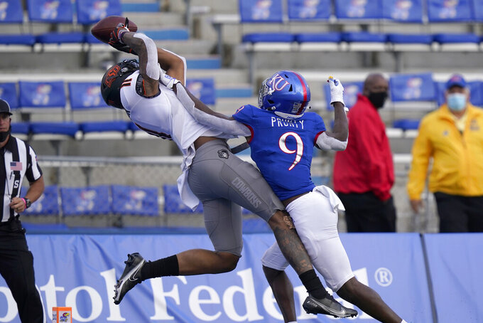 Kansas cornerback Karon Prunty (9) breaks up a pass intended for Oklahoma State wide receiver Dee Anderson (11) during the second half of an NCAA college football game in Lawrence, Kan., Saturday, Oct. 3, 2020. (AP Photo/Orlin Wagner)