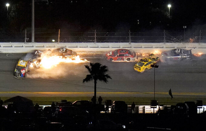Racers crash during the last lap in the NASCAR Daytona 500 auto race at Daytona International Speedway, Monday, Feb. 15, 2021, in Daytona Beach, Fla. Joey Logano (22) was leading before the wreck; Brad Keselowski (2) was in second. (AP Photo/Chris O'Meara)