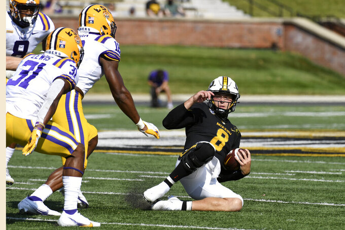Missouri quarterback Connor Bazelak (8) slides as LSU linebacker Damone Clark and safety Cameron Lewis (31) defend during the first half of an NCAA college football game Saturday, Oct. 10, 2020, in Columbia, Mo. (AP Photo/L.G. Patterson)