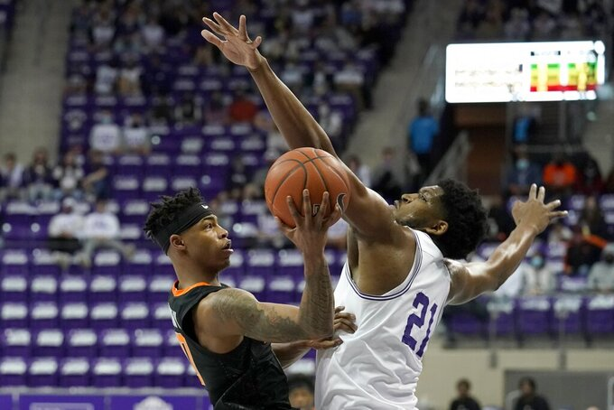 Oklahoma State guard Avery Anderson III (0) shoots as TCU's Kevin Samuel (21) defends during the first half of an NCAA college basketball game in Fort Worth, Texas, Wednesday, Feb. 3, 2021. (AP Photo/Tony Gutierrez)