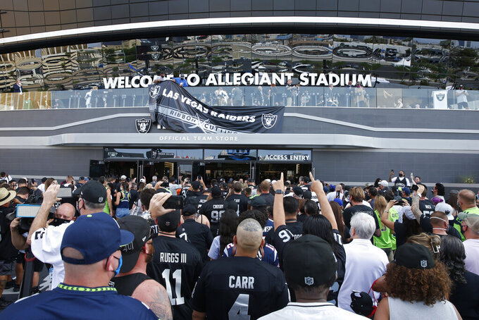 Fans enter Allegiant Stadium before an NFL preseason football game between the Las Vegas Raiders and the Seattle Seahawks, Saturday, Aug. 14, 2021, in Las Vegas. (AP Photo/Steve Marcus)