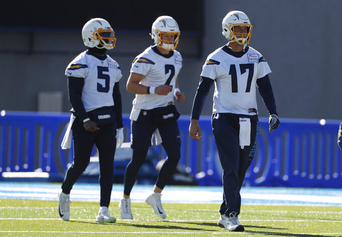 From left, Los Angeles Chargers quarterbacks Tyrod Taylor, Easton Stick and Philip Rivers take part in a drill during an NFL football practice Thursday, Nov. 14, 2019, at Air Force Academy, Colo. The Chargers are training at Air Force, which is at an elevation of 7,200 feet, to prepare for Monday night's game against Kansas City in Mexico City. (AP Photo/David Zalubowski)