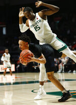 Miami center Ebuka Izundu, right, tries not to foul Pittsburgh guard Trey McGowens, left, as he grabs a rebound during the first half of an NCAA college basketball game, Tuesday, March 5, 2019, in Coral Gables, Fla. (AP Photo/Wilfredo Lee)