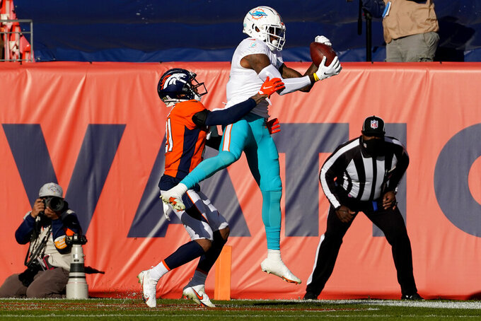 Miami Dolphins wide receiver DeVante Parker pulls in a touchdown pass as Denver Broncos cornerback A.J. Bouye, left, defends during the first half of an NFL football game, Sunday, Nov. 22, 2020, in Denver. (AP Photo/Jack Dempsey)