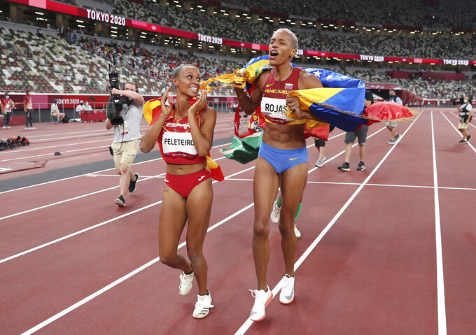 Gold medalist Yulimar Rojas of Venezuela, right, and bronze medalist Ana Peleteiro of Spain, celebrate on the track following the final of the women's triple jump at the 2020 Summer Olympics, Sunday, Aug. 1, 2021, in Tokyo, Japan. (Christian Petersen/Pool Photo via AP)