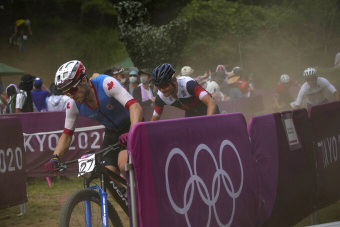Peter Disera of Canada rides at the start of the men's cross country mountain bike competition at the 2020 Summer Olympics, Monday, July 26, 2021, in Izu, Japan. (AP Photo/Christophe Ena)