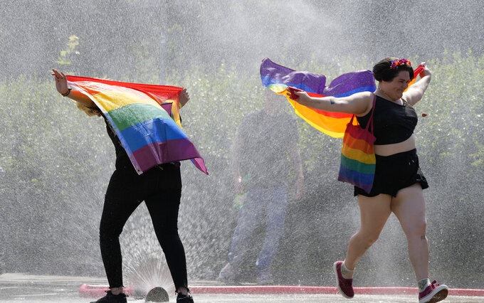 A women with a rainbow flag cools off in a sprinkler ahead of the Equality Parade, the largest LGBT pride parade in Central and Eastern Europe, in Warsaw, Poland, Saturday, June 19, 2021.(AP Photo/Czarek Sokolowski)