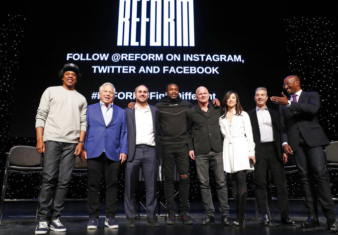 "Entrepreneur and recording artist Shawn ""Jay-Z"" Carter, from left, poses with New England Patriots owner Robert Kraft, Philadelphia 76ers co-owner and Fanatics executive chairman Michael Rubin, recording artist Meek Mill, Galaxy Digital CEO and founder Michael Novogratz, Brooklyn Nets co-owner Clara Wu Tsai, Third Point CEO and founder Daniel S. Loeb, and REFORM Alliance CEO and political activist Van Jones after the group announced a partnership to transform the American criminal justice system, Wednesday, Jan. 23, 2019, in New York. (AP Photo/Kathy Willens)"