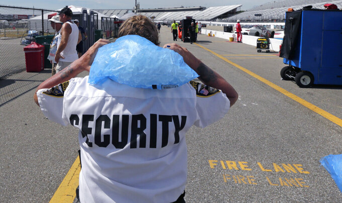 Track security officer Patty Patterson carries a bag of ice on her shoulders as she walks back to her post during a NASCAR Cup Series auto race practice at New Hampshire Motor Speedway in Loudon, N.H., Saturday, July 20, 2019. Temperatures were forecasted to reach nearly 100 degrees at the track. (AP Photo/Charles Krupa)