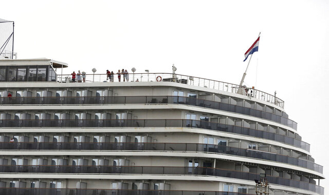 Passengers stand on the top deck of the MS Westerdam while the cruise ship is docked in Sihanoukville, Cambodia Monday, Feb. 17, 2020. The feel-good story of how Cambodia allowed a cruise ship to dock after it was turned away elsewhere in Asia for fear of spreading the deadly virus that began in China has taken a dark turn after a passenger released from the ship tested positive for the virus. (AP Photo)